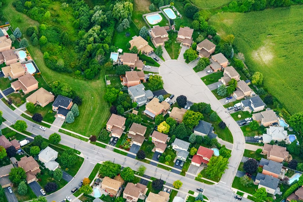 Aerial view of houses in residential suburban neighborhood surrounded by green grass and land.