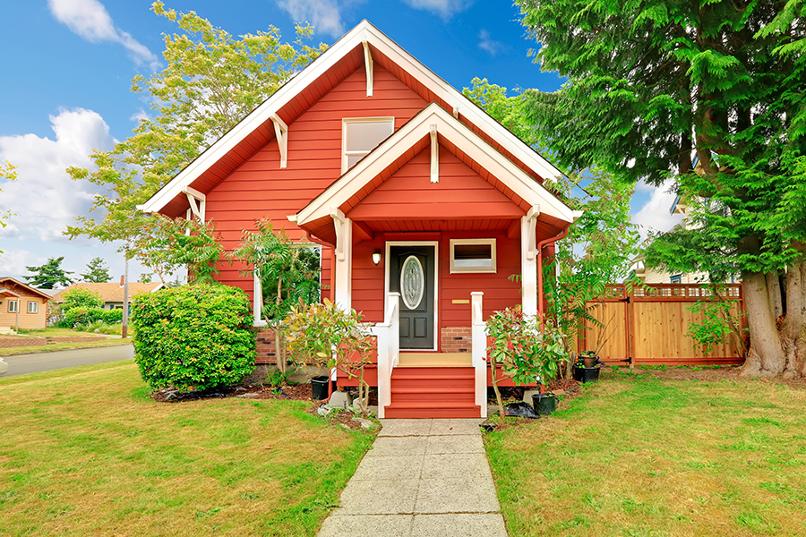 Small coutnryside house exterior in bright red color with white trim. Entrance porch with stairs and white railings